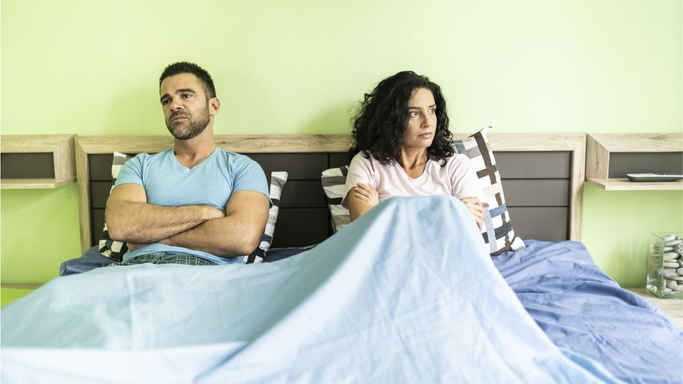 Couple looking sitting on a bed