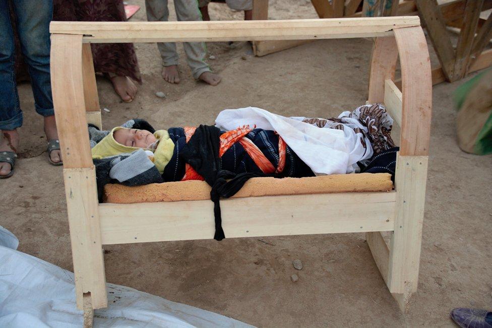 Beba u priručnoj kolevci u kampu za izbeglice